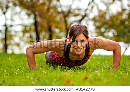 A caucasian female doing push ups in the park - stock photo