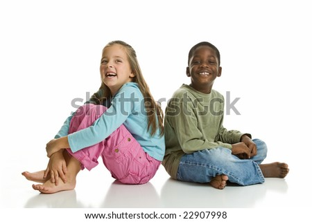 A Caucasian girl and an African American boy smiling for the camera. Isolated on a white background. - stock photo