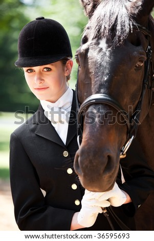 A caucasian girl getting ready for a horseback riding posing with her horse - stock photo