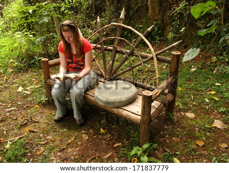 A caucasian girl reads a book while sitting on a wooden bench in the forest