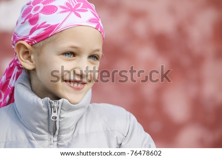 a caucasian girl wearing a head scarf as a result of hair loss due to chemotherapy