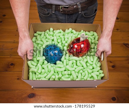 A caucasian male holding a cardboard box full of packing peanuts and two piggy banks. - stock photo