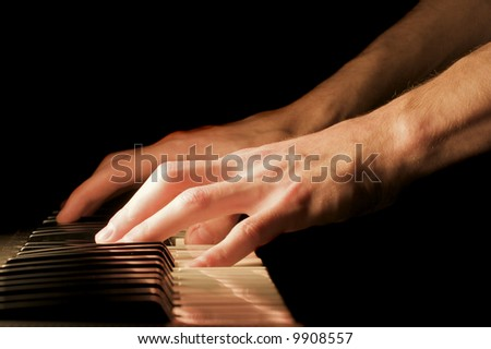 A caucasian male's hand playing a keyboard - stock photo
