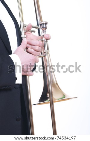 A caucasian male wearing a tuxedo holds a trombone.  Isolated on white. - stock photo