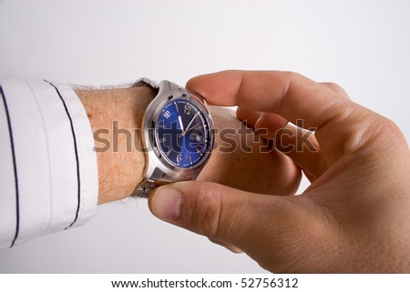 A caucasian man checking the time on his silver watch with a blue face