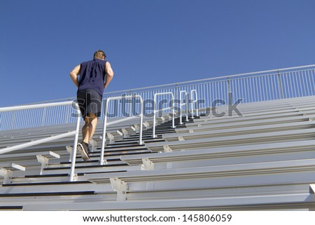 A Caucasian man in his twenties works out at a stadium. - stock photo