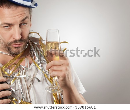 A caucasian man is drunk . He has a bottle in his hand  and a glass with sparkle wine. - stock photo