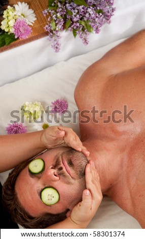 A Caucasian man lies on a massage table getting a massage with cucumbers on his eyes. - stock photo