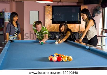 a caucasian man teaching pool to asian women - stock photo