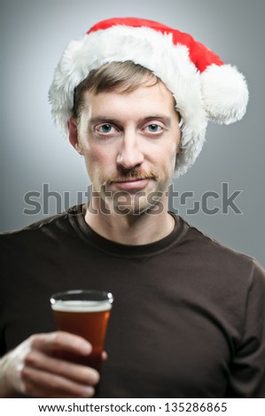 A Caucasian man wearing a Santa hat reluctantly toasts with a pint of beer. - stock photo