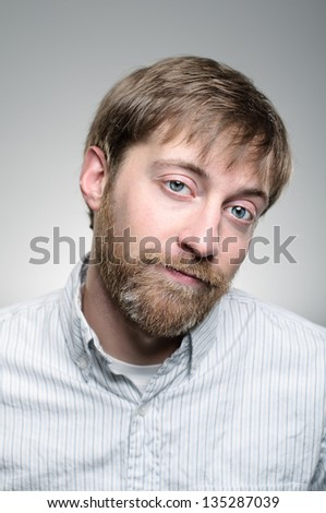 A Caucasian man with a beard blowing his cheeks. - stock photo