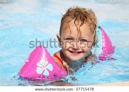 a caucasian pretty little child swimming in a swimming pool wearing armbands to keep her afloat - stock photo