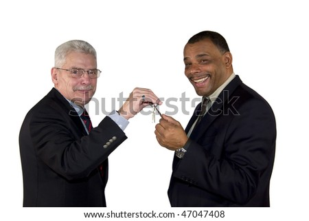 a caucasian senior manager handing over a key to his partner, an African-American mature businessman, isolated on white background - stock photo
