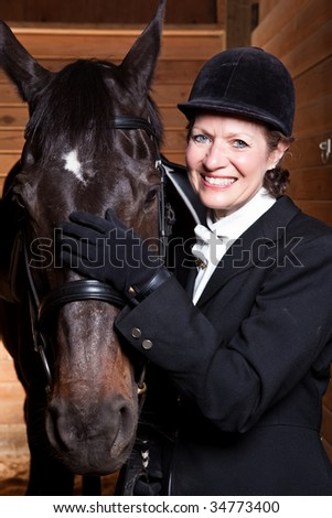 A caucasian senior woman with her horse indoor - stock photo