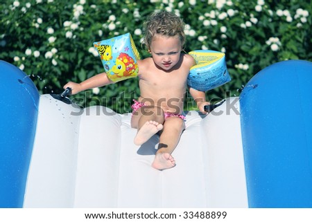a caucasian toddler in armbands coming down a waterslide - stock photo