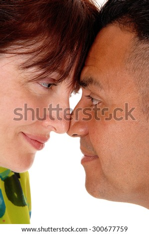 A caucasian woman and her hispanic husband putting there foreheadtogether in closeup, isolated for white background. - stock photo