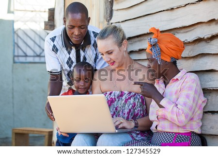 A caucasian woman are showing to African people something on the laptop. - stock photo