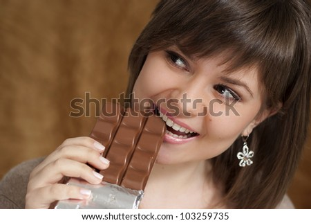 A Caucasian woman eats chocolate brown background - stock photo