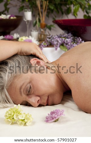 A Caucasian woman lies on a massage table getting a massage. - stock photo