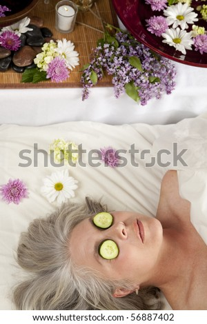 A Caucasian woman lies on a massage table with cucumber on her eyes. - stock photo