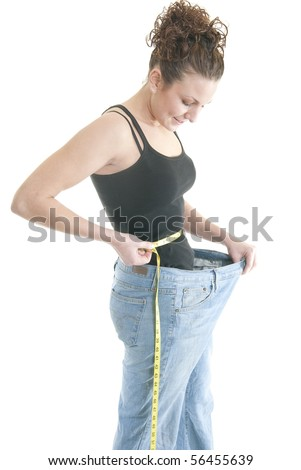 A Caucasian woman measures her waist while wearing pants that are too large.