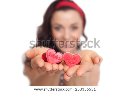A caucasian Women is smyling and hold some hearts in her hands. isolated on white.  Bokeh background.  - stock photo