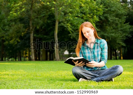 A Caucasian young Christian woman reading a Bible outdoors in a public park. - stock photo