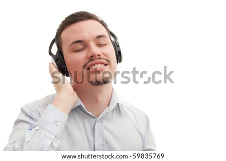 A causasian male blissfully listening to music on his headphones - stock photo