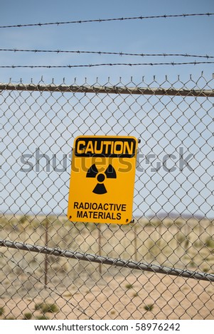 A Caution Radioactive Materials Sign posted on a fence. - stock photo