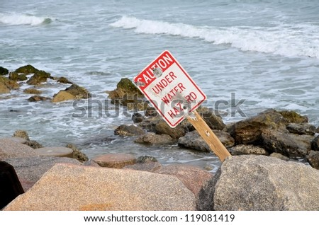 A caution sign along the rocky shore in North Carolina - stock photo