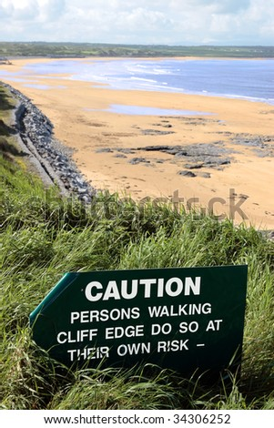 a caution sign on a cliff edge in ballybunion - stock photo