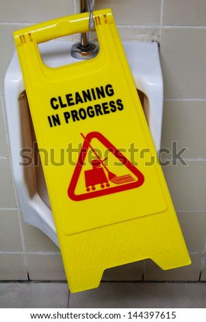 A Caution Sign warns people of a clean floor in  the men's restroom - stock photo