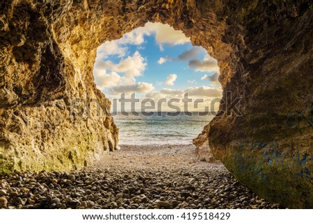 A cave on the ocean at sunset. - stock photo