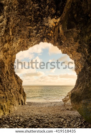 A cave on the ocean at sunset - vertical. - stock photo