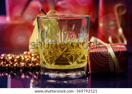 a celebration moment of Christmas or New Year`s Eve where a glass with alcohol is surrounded by decoration ornaments or gifts