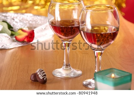A celebratory dinner with a rose, candle,  two glasses of red wine - stock photo