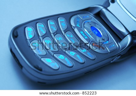 A cell phone key pad with cool blue lighting. - stock photo