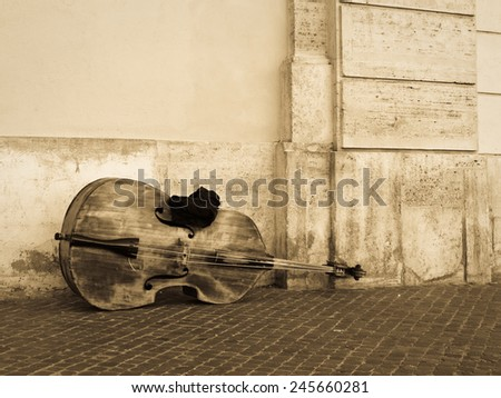 A cello or contrabass left out on the street before playing - stock photo