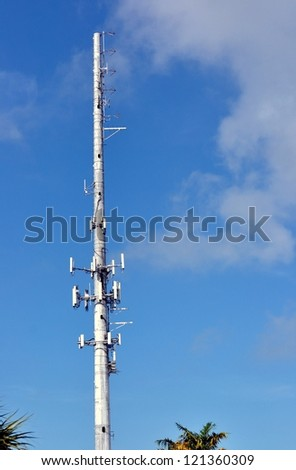 A Cellular Phone Tower With Palm Trees Against Blue Sky With Clouds - stock photo