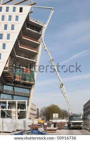 A cement truck with mounted pump is pumping concrete to the top floor of a highrise - stock photo