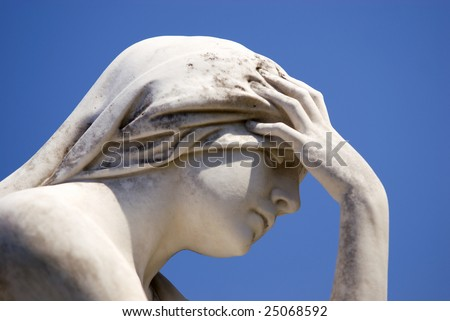 A cemetery statue of a mourning woman closeup, with solid dark blue sky background  Location Mount Olivet Cemetery Nashville TN  copy space - stock photo