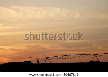 A center modern pivot irrigation system in a cultivated land farm field at sunset - stock photo
