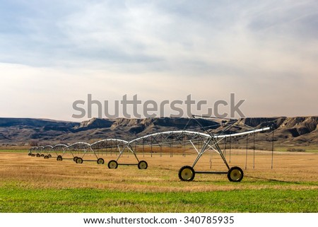 A center pivot irrigation unit in a western field surrounded by bluffs on a sunny day.