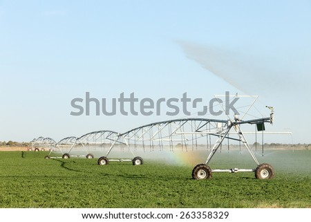 A center pivot sprinkler used to irrigate an alfalfa field. - stock photo