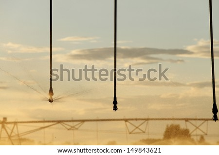 A center pivot used to irrigate a farm field. - stock photo