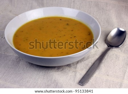 A ceramic bowl of soup made from carrots and coriander