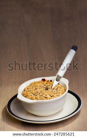A ceramic dish with freshly baked mixed berry crumble, and a spoon stuck in to the berry crumble. - stock photo