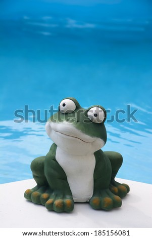 a ceramic frog in front of the the blue water of a swimming pool - stock photo