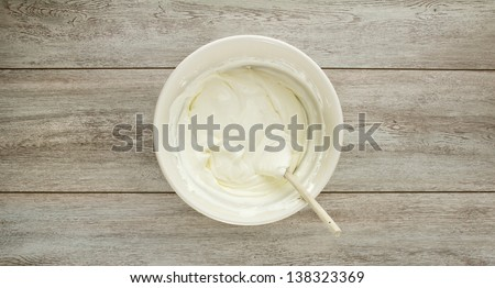 A ceramic ivory mixing bowl of cream soft cheese, mixed with a wood spoon on weathered boards. - stock photo