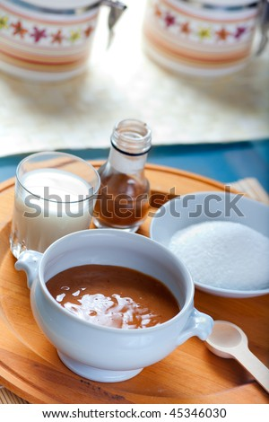 A ceramic pot of Cajeta, the famous mexican caramel sauce with ingredients and wooden spoon - stock photo